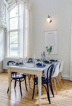 Dans cette pièce au plafond haut, la fenêtre est absolument majestueuse. Une table et des chaises de récup avoisinent des Eames pour un décor unique.