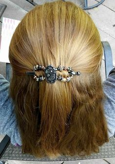 Half up hairstyle with a beautiful, innovative barrette ~ Steampunk flexi clip featuring a floral design with mechanical details in mixed metals of gunmetal gray, silver, gold, and rose gold. She glows in Lilla Rose!