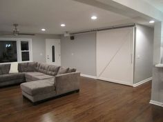 behr gentle rain wall color. love the barn door and the big couch.