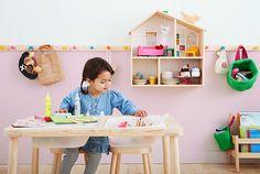 Ein Kind sitzt an IKEA FLISAT Kindertisch und malt. Alle FLISAT Möbel bestehen aus langlebigem Kiefernholz. Hier zu sehen FLISAT Puppenhaus/Wandregal.
