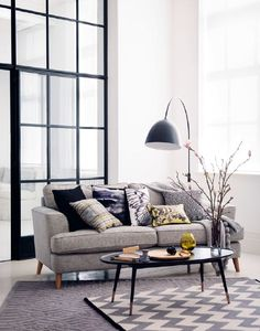 A modern living room showcasing grey sofa and a contemporary coffee table and floor lamp with printed monochrome cushion and rug.