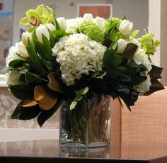 A great arrangement year-round; tulips, hydrangeas, viburnum, orchids, and magnolia leaves come from multiple seasons. Home Flowers, Fresh Flowers, Beautiful Flowers, Cut Flowers, Orchid Arrangements, Flower Arrangement, Fresh Flower Delivery, Magnolia Leaves, Flower Decorations