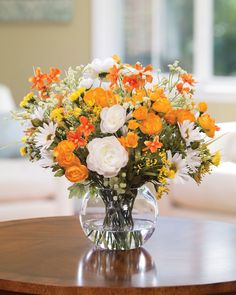 Orange and yellow always make a happy, sunny combination of flower colors. Mini cosmos, ranunculus, and daisy gather with baby's breath and statice in a glass ball vase with our crystal clear acrylic water. Imagine the sunshine this silk flower centerpiece will bring to your morning table.