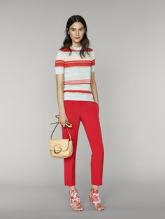 These cropped pants are paired perfectly with a colorful multi-striped short sleeve top. The look is completed with a beige purse and patterned fringe heels | Banana Republic Summer '16