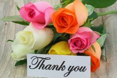 Thank you note with colorful rose bouquet on white wooden surface