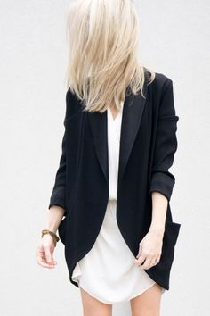 Long black blazer with curved hem, worn with a short white dress; modern chic style