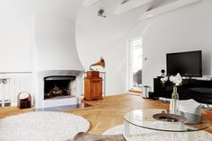 Lounge Area With Fireplace And Rounded Glass Top Coffee Table