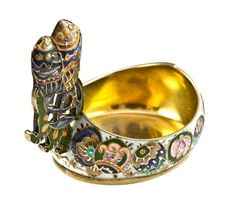 A Fabergé silver-gilt and cloisonné enamel kovsh, the body of traditional form decorated in the pan-slavic style with varicoloured geometric designs on a white enamel background, the raised handle in the form of stylised owls sitting on a perch of abstract design, marked 88 zolotniks, signed Fabergé, Moscow, approximately 5½cm in diameter, gross weight 1.91 ounces, circa 1908-1917.