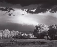 1958 Autumn Storm, Las Trampas, near Peñasco, New Mexico [distant church with belltower amid cottonwoods?, highlit by sun; dark sky with sun catching cloud layer above horizon] by Ansel Adams 78.152.32