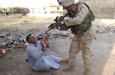 A U.S. soldier aims his weapon at a man who a soldier had just shot in the neck as he attempted to flee down a narrow alley in a van, across the street from the scene of Tuesday's intense shootout on a house in Mosul, Iraq on Wednesday, July 23, 2003. (AP Photo/Wally