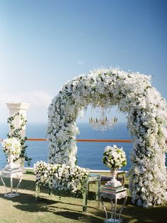 Lush white floral arbor with suspending chandelier // A Greek Garden Recreated: Erwin and Airin's Wedding at The Edge, Bali