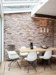 Salle a manger avec murs de briques et chaises Eames