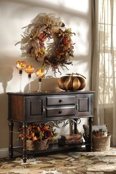 Fall decor at it's finest here with the beautiful wreath on the wall, a candle…