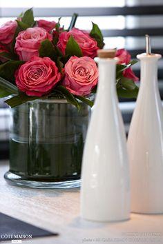 2 vases blancs et un pot de fleurs qui regorge de roses en guise de déco.