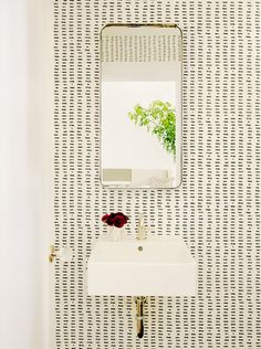 Text on wallpaper in black and white bathroom with small floral arrangement on sink