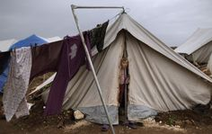 A Syrian girl, whose family fled their home in Idlib, looks out of a tent tent, at a camp for displaced Syrians, in the village of Atmeh, Syria, Monday, Dec. 10, 2012. (Photo by Muhammed Muheisen/AP)