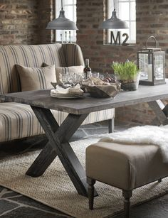 Rustic French Country...living space...blue & cream striped sofa...weathered wood table...textured rug...old brick wall & industrial metal lights.