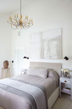 Designer James Huniford transforms a 1910 farmhouse into a contemporary home with neutral hues, antique pieces like this chandelier, and modern accents like art and new fixtures. Love the end result!