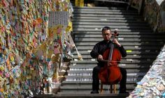 David Wong performs in front of a wall posted with messages of support for pro-democracy protesters at Admiralty district