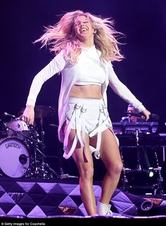 Looking lean: Ellie flaunted her silky smooth stems and her sculpted stomach in the outfit which comprised hot pants and crop top
