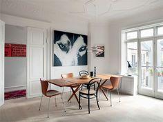 Wegner spisebordet er omgivet af Arne Jacobsens 7'ere i naturlæder og sorte Thonet stole. Det fantastiske ulve-maleri er en del af serien Animal Faces.
