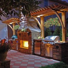 Gorgeous In-Line #Outdoor #Kitchen with stainless steel appliances fireplace brick oven. Get more Outdoor Kitchen Tips...