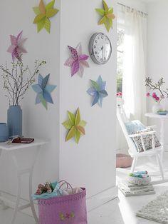 Kreative Raumgestaltung durch Blumen an der Wand? Warum eigentlich nicht! Einfarbige Wände lassen sich mit Wandschmuck aus Origami frühlingshaft dekorieren: Basteln Sie sich große Blumen aus gemusterten Papier und lassen Sie Ihre Wohnung aufblühen!