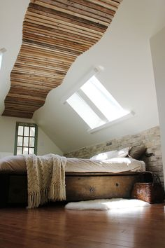Bedroom with skylights, a walkway on the ceiling, platform bed and a little sheepskin rug | via Not A Paper House