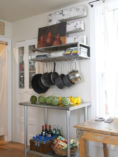 Wondering how to make the best use of a narrow slice of blank wall in your kitchen? Transform it with a modular baker's rack. A counter-height metal table serves as prep and storage space. Above, a wall-mount pot rack keeps beloved cookbooks and necessary pots and pans within easy reach. Be sure to hang the shelf high enough to give the cookware enough clearance to hang down.