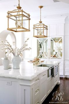 Stunning white transitional kitchen with brass chandeliers faucets pot filler and handles. Two-toned La Cornue stove. Stunning white transitional kitchen with brass chandeliers faucets pot filler and handles. Two-toned La Cornue stove. Kitchen Nook, White Kitchen Cabinets, New Kitchen, Kitchen White, Kitchen Ideas, Kitchen Themes, Island Kitchen, Kitchen Sinks, Country Kitchen