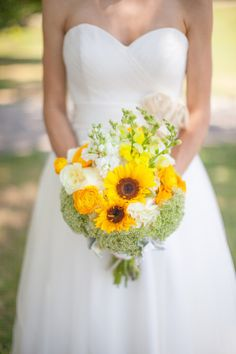 Leah carried a yellow, white, and green bridal bouquet which included sunflowers, snap dragons, Queen Anne's lace, stock, hydrangea, ranunculus, dusty miller and white garden roses which was wrapped in twine. Flowers by Dorothy McDaniel's Flower Market