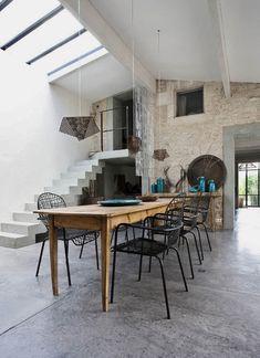 Salle à manger à la fois rustique et design - de grands murs de pierre, une table ancienne en bois, mais un sol et des escaliers en béton, des chaises et suspensions en métal.  #dining room #stone wall #concrete