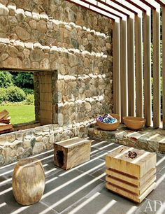 Stools by Chista are grouped before the fireplace in the sunken conversation space; the baskets are by Calvin Klein Home.