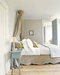 Look to soft grays, putty tones, or even a diluted violet for a serene and versatile palette. The colors -- along with black and white -- make it easy to swap in and out furniture and accessories in your space. The flexible color scheme will allow you to adopt different looks throughout the year. A bedroom is covered with a mouse gray to match the bed-linen drapery.