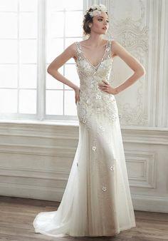 The perfect combination of elegance and romance combine in this tulle A-Line wedding dress, complete with three-dimensional floral appliqués, sparkling Swarovski crystals, and illusion tank sleeves. Intricate patterns of Swarovski crystals adorn an unexpected sheer plunging back. Finished with crystal button over zipper closure.