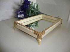 Bandeja com base de MDF decorado com manta de strass dourado e meia pérolas. Pés egípcios e espelho na base interna.