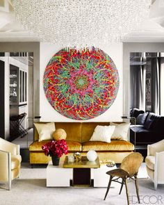Living room with white walls, gold chairs, gold couch, white throw pillows, white and gold coffee table, flowers, large colorful artwork, and a large flush mount chandelier