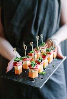 Drizzle this Melon, Blue Cheese, Prosciutto, and Basil Canapés recipe with balsamic to pack in the flavor.