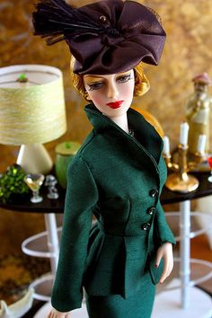 "Lady Director Ivy Jordan wears the emerald green suit from ""The Perfect Gift"", an Ashton Drake produced fashion designed by Regina Ganem circa 1947, and the hat from the Madra Lord fashion ""So Evil My Love"", designed by Tim Kennedy, also circa 1947."