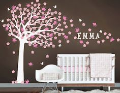 Pink and brown baby girls room with tree wall decal.