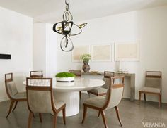 """He unites the curves of a minimalist columnar table with graceful Regency-style chairs and the Calder-esque swoops of an Hervé Van der Straeten light fixture in a dining room that also contains artwork by Donald Judd and Robert Wilson. """"I love a touch of chaos,"""" he says of the exuberant chandelier. """"Things shine better when they are living with opposites."""" Juxtapositions such as Regency-style chairs with a minimalist table create visual interest in the dining room. Table, J. Robert Scott…"""