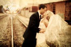 Bride and groom posing on railroad tracks in Royal Oak Michigan