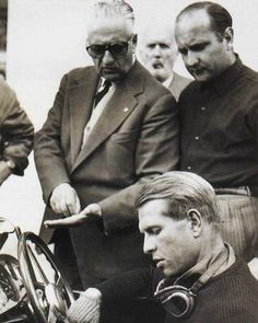 Help! I identify Enzo Ferrari; the guy next to him seems to be Juan Manuel Fangio (if I'm correct, we can date the picture, as Fangio drove for Ferrari in 1956 only). But who's the blond guy sitting down? My guess is Wolfgang von Trips. But it could also be Paul Frere...