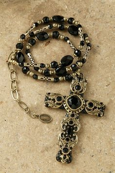 This cross is as versatile as it is elegant. Black Jewels and crystals set in gold with a chain to match makes this the perfect accessory to wear to accent your apparel or to be the centerpiece of it.