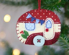 Handmade vintage caravan Christmas ornament. Vintage caravan trailer hanging ornament, handmade from felt and decorated with fabric scraps. With tiny felt bunting and buttons for the wheel and door knob. Vintage red and cream. Blanket stitched edges and a cotton loop for hanging.