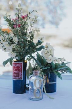 Wine-bottle wedding centerpiece idea - repurposed wine bottles with greenery and white flowers {Michael Stephens Photography}
