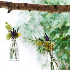 ENSIDIG/エンシーディグ 花瓶に春の花を挿し、木の枝からつり下げた画像。