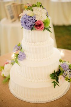 Beautiful cake with fresh flowers.  Love the details on each layer.  Consider letting the wedding cake reflect details from your wedding dress.