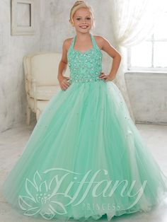 A full tulle skirt with scattered twinkling ornaments makes this Tiffany Princess pageant dress 13446 the crown winning. A halter sweetheart neckline tops off the rhinestone, beaded bodice. A partially open back is enhanced by a functional lace up design. Features:  Silhouette: A-Line Ball Gown  Neckline: Halter/Sweetheart  Fabric: Beaded/Tulle Sizes Available: 0 through 16   Colors Available: Mint, Shocking Pink and White