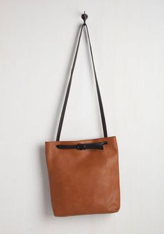 On your quest for the best view in New England, you employ this vegan faux-leather tote as your stylish accomplice. Hauling your camera and sunnies within its removable zippered pouch, and stowing your maps in its spacious interior, this caramel-and-black bag has your adventure essentials covered!